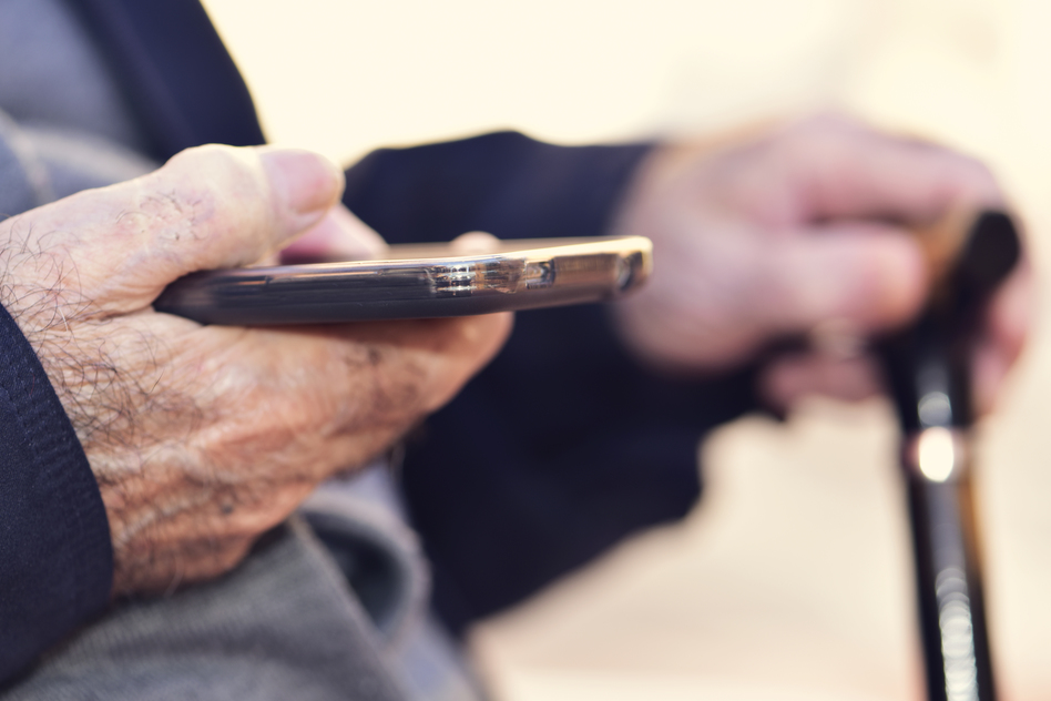 closeup of an old caucasian man with a walking stick in his hand using a smartphone