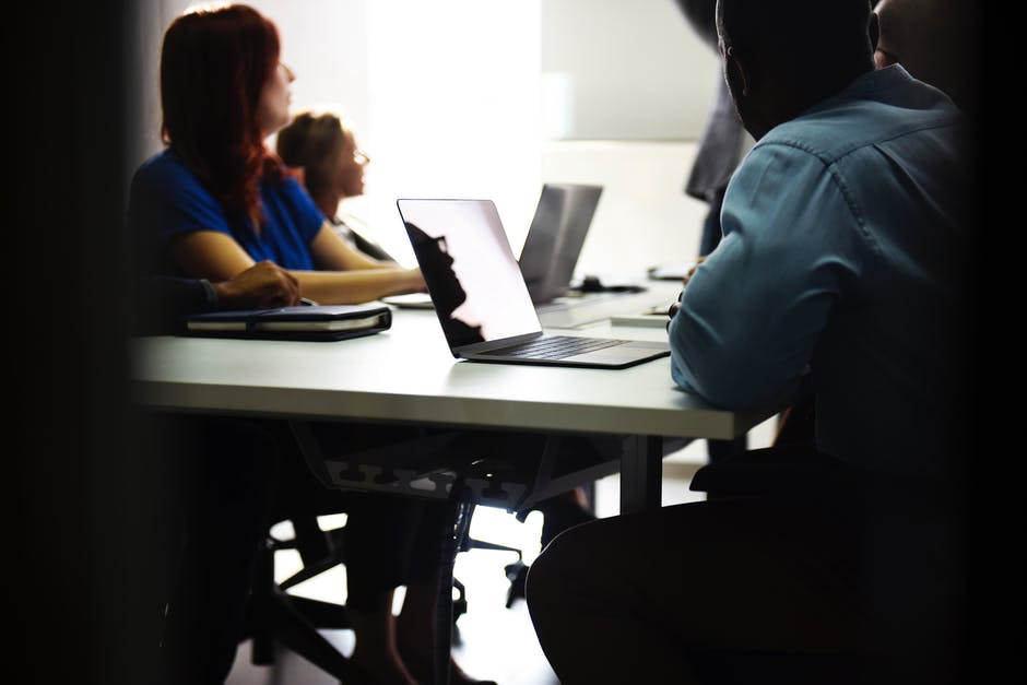 Diverse individuals round a desk, listing what makes their financial website distinct