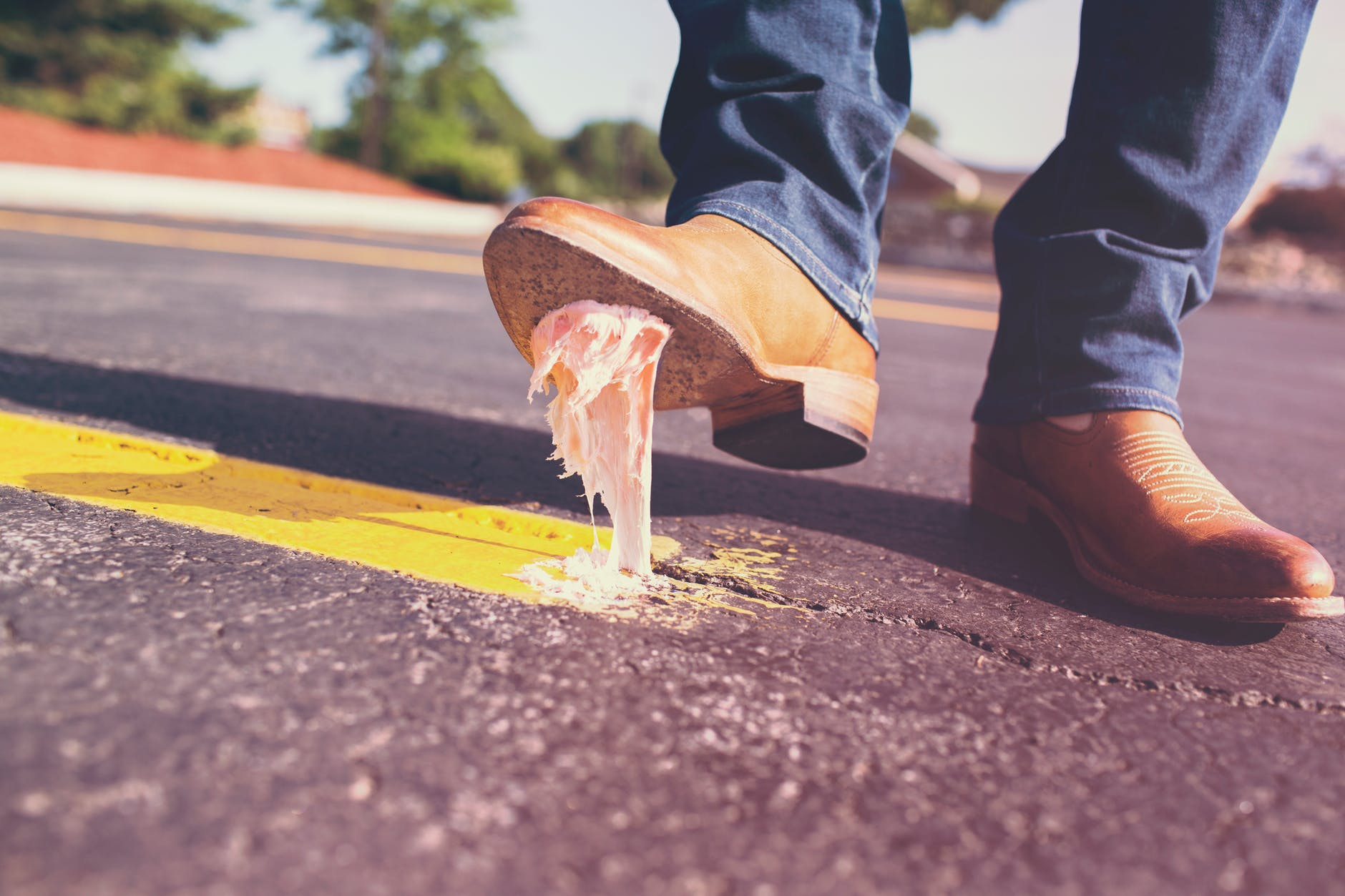 Man stepping on chewing gum, illustrating mistakes with financial logo design