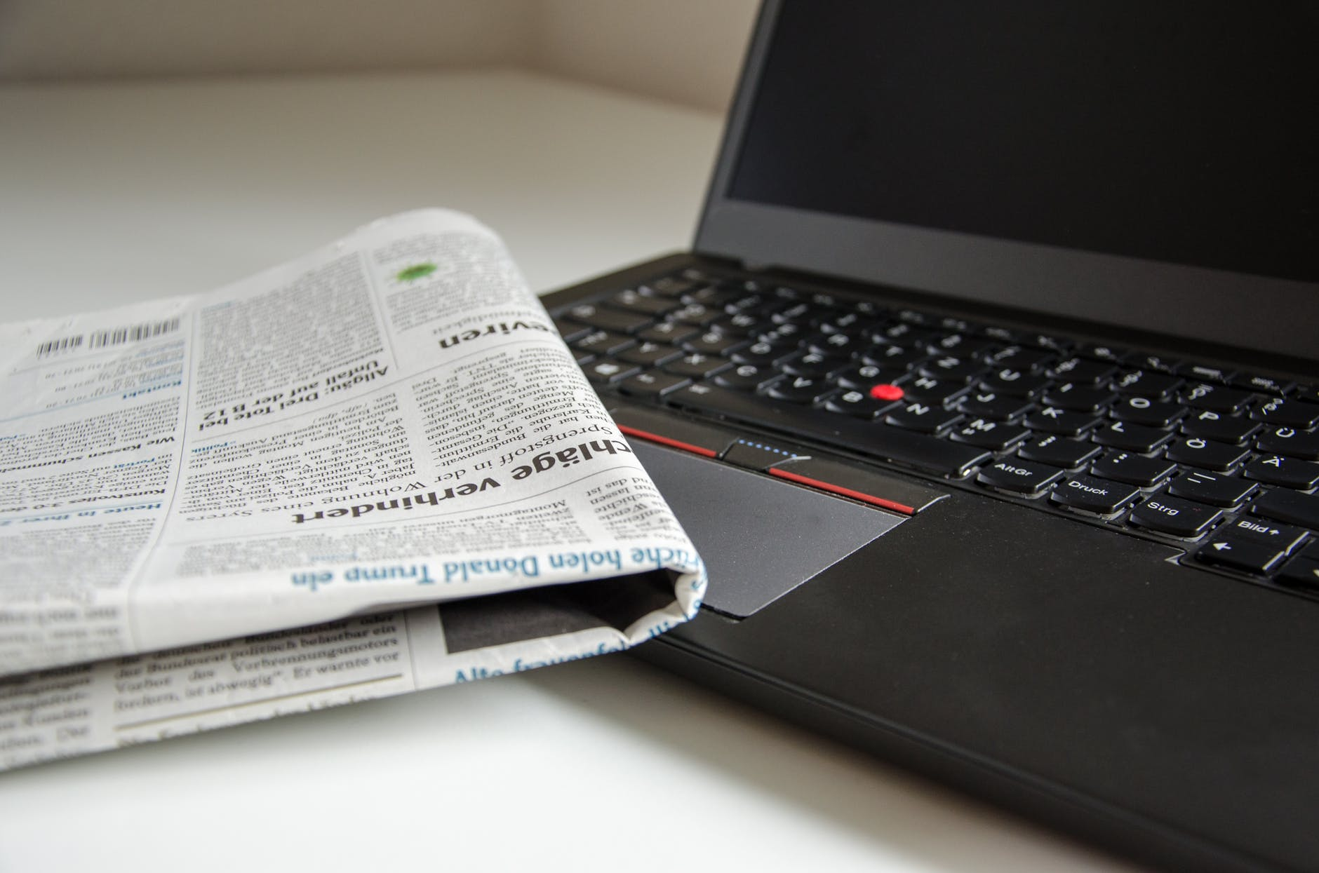 Picture of a laptop and a printed financial newsletter